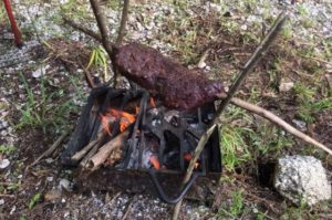 ブッシュクラフトの肉焼き機に鹿肉を刺して焼いている